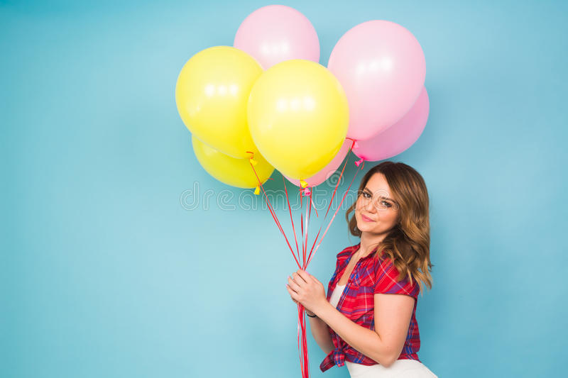 Summer holidays, celebration, woman and people concept - happy woman with colorful balloons indoors, background with royalty free stock images
