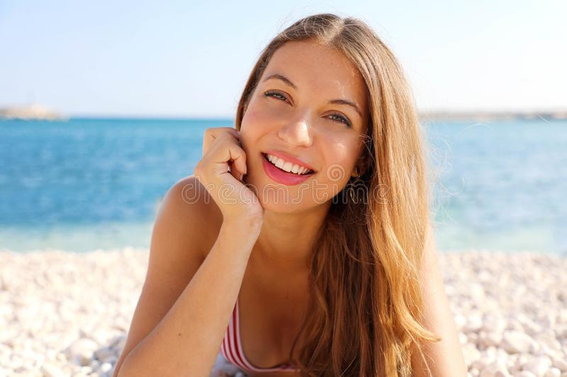 Summer holidays concept. Beauty young smiling woman enjoying relax lying on the beach looking at camera stock photo
