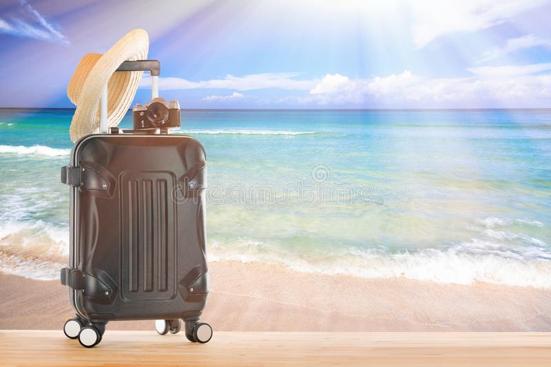 Summer holidays concept. Suitcase baggage with straw hat and retro camera against sandy tropical beach and turquoise water ocean. Blue sky and sunlight stock images