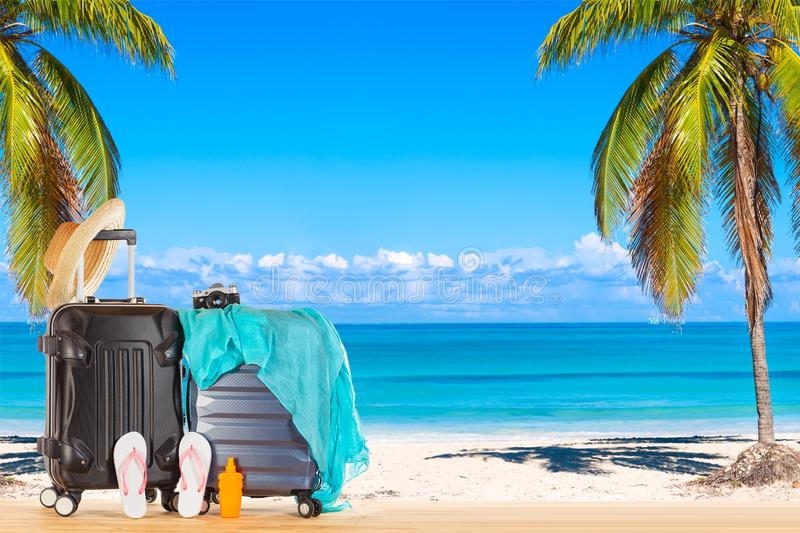 Summer holidays concept. Suitcases baggage with straw hat, blue pareo, flip flops, sunscreen lotion bottle and retro camera royalty free stock photo