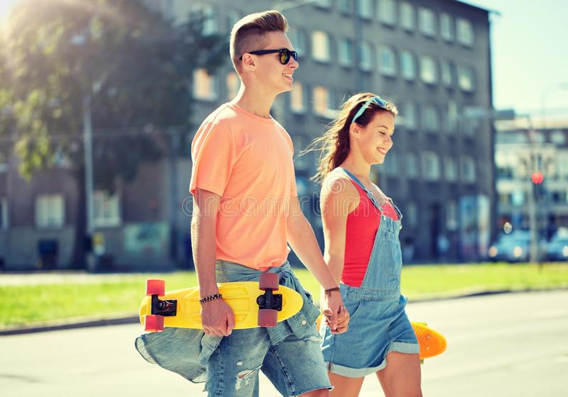 Teenage couple with skateboards on city street. Summer holidays, extreme sport and people concept - happy teenage couple with short modern cruiser skateboards royalty free stock photography