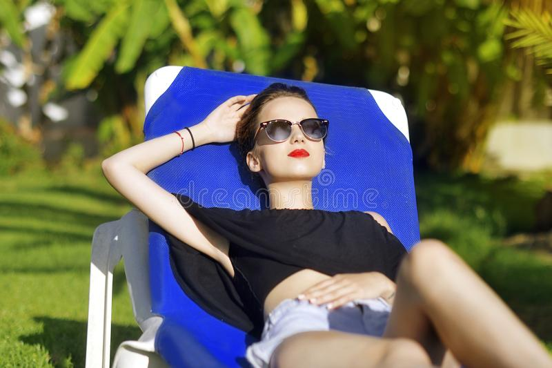 Summer holidays . Fashion girl in sun glasses is relaxing.In the background a palm tree. Vacation concept. Beautiful girl lies on royalty free stock photography