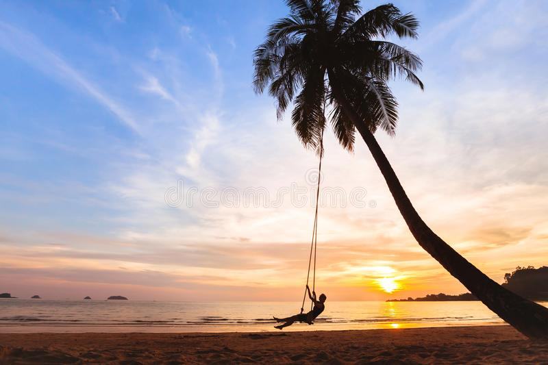 Summer holidays, happy woman on the swing on tropical beach , vacation stock photos