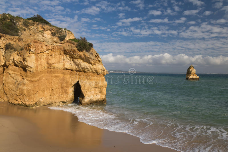 Summer holidays idea travel to sandy camilo beach. Wonderful natural erosion of stunning sea caves cliffs on sandy camilo beach, algarve, portugal royalty free stock image
