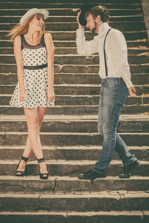 Loving couple retro style flirting on stairs. Summer holidays love relationship and dating concept - romantic playful couple retro style flirting on city stairs royalty free stock images