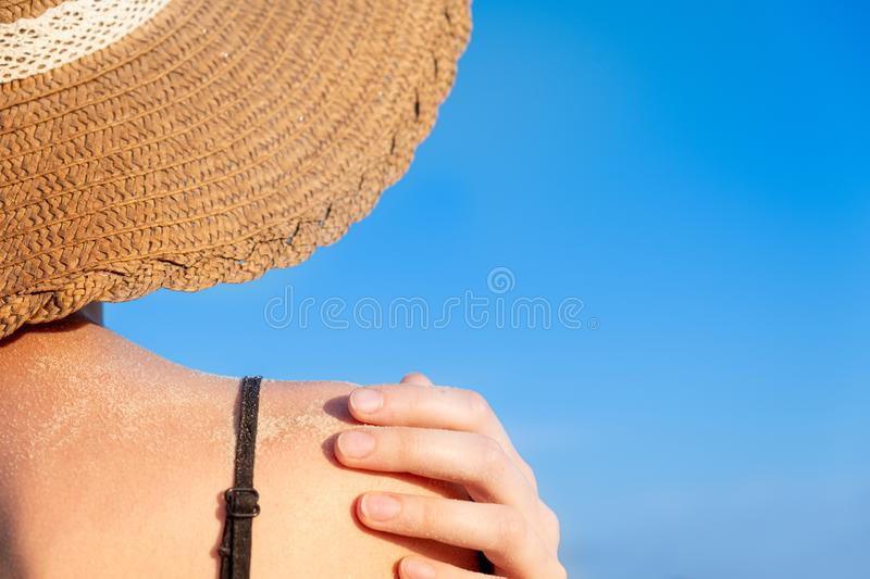 Summer holidays mood: female shoulder covered in sand in bright blue background. stock image