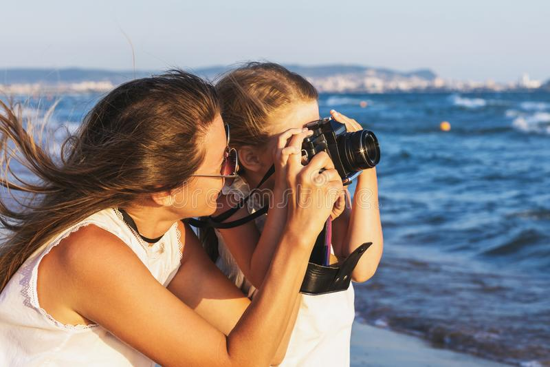 Summer holidays: mother and daughter take pictures of sights while walking near the sea. Closeup royalty free stock image