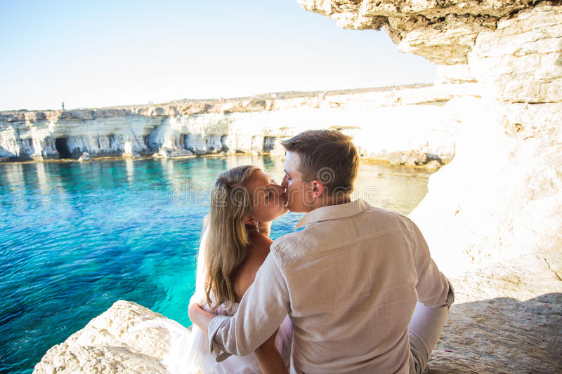 Summer holidays, people, love and dating concept - happy couple hugging and kissing at summer sea background royalty free stock photo
