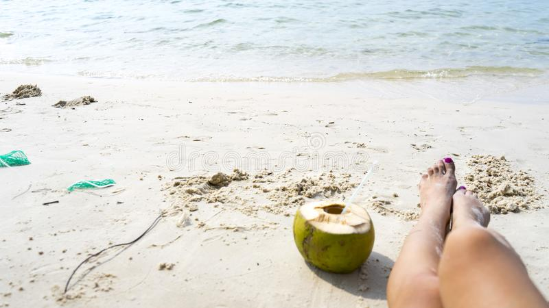 Coconut and legs on the white beach royalty free stock photos