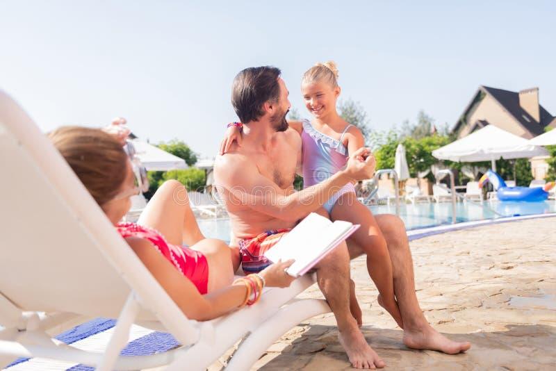 Positive joyful family resting near the swimming pool stock images
