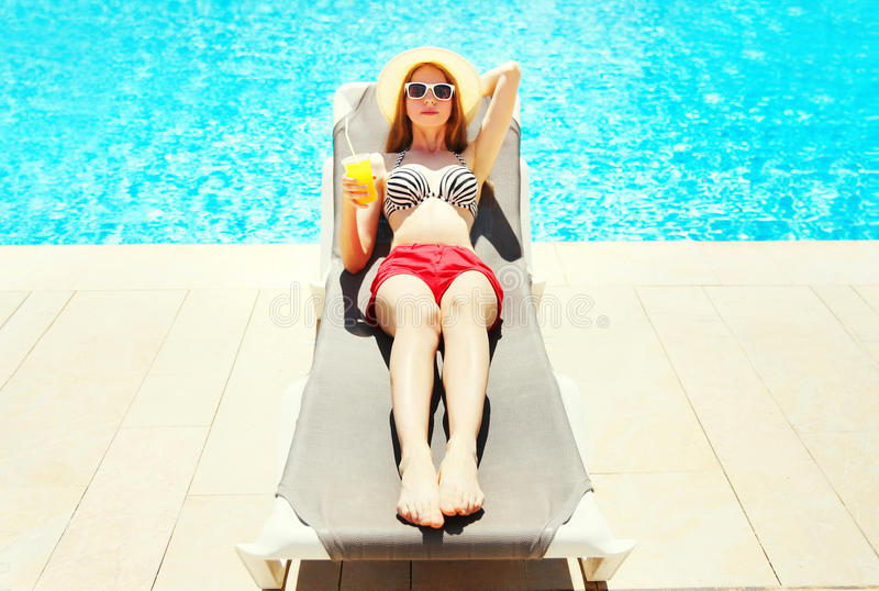 Summer holidays - pretty woman resting with juice from cup on a deckchair. Over a blue water pool background stock photos