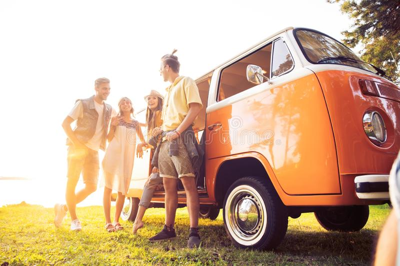 Summer holidays, road trip, vacation, travel and people concept - smiling young hippie friends having fun over minivan stock photography