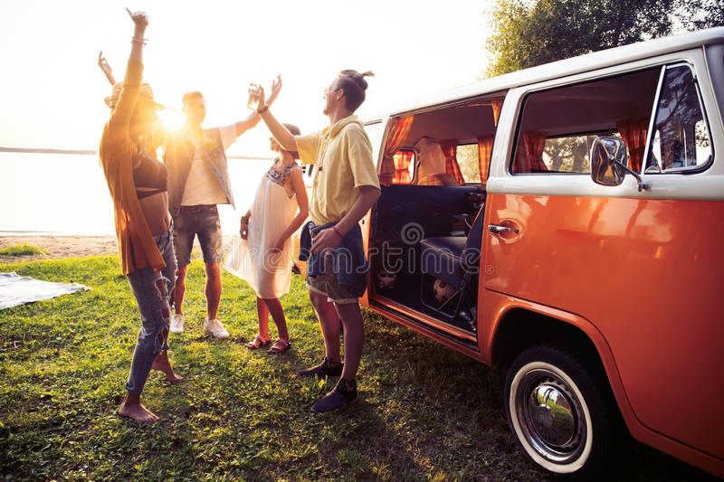 Summer holidays, road trip, vacation, travel and people concept - smiling young hippie friends having fun over minivan. Friends dancing in the light of sunset royalty free stock images