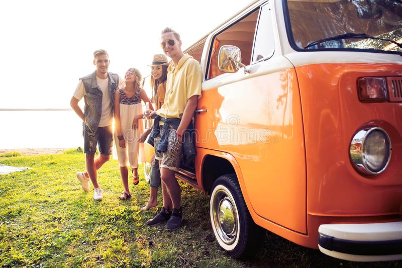 Summer holidays, road trip, vacation, travel and people concept - smiling young hippie friends having fun over minivan royalty free stock image