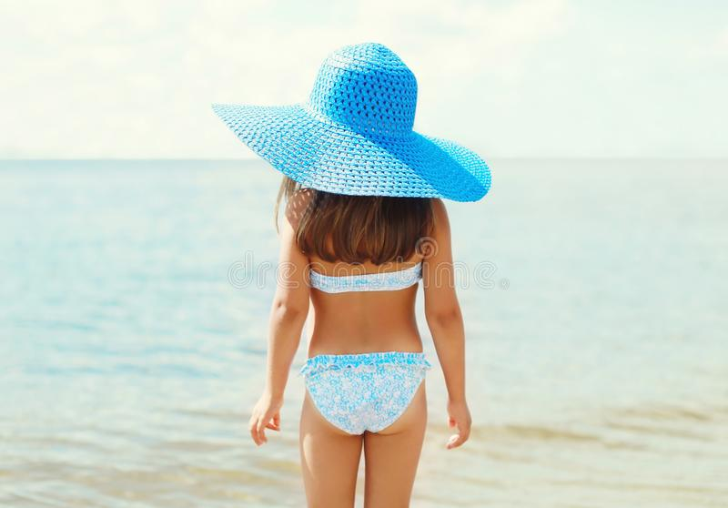 Summer holidays, vacation concept - little girl in straw hat on beach over sea stock images