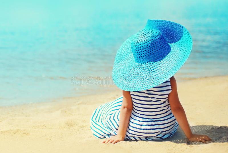 Summer holidays and vacation concept - little girl in striped dress, straw hat enjoying sitting on sand beach royalty free stock image