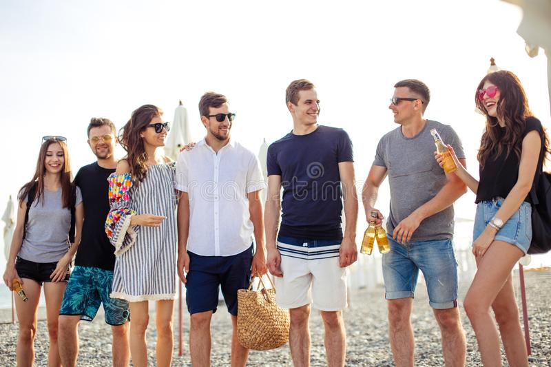 Holidays, vacation. group of friends having fun on beach, walking, drink beer, smiling and hugging stock images
