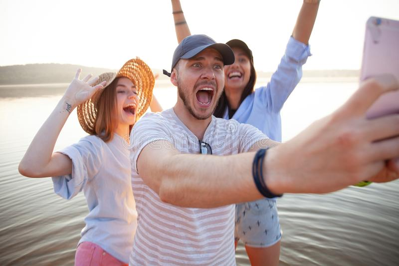 Summer, holidays, vacation and happiness concept - group of friends taking selfie with smartphone. stock photos