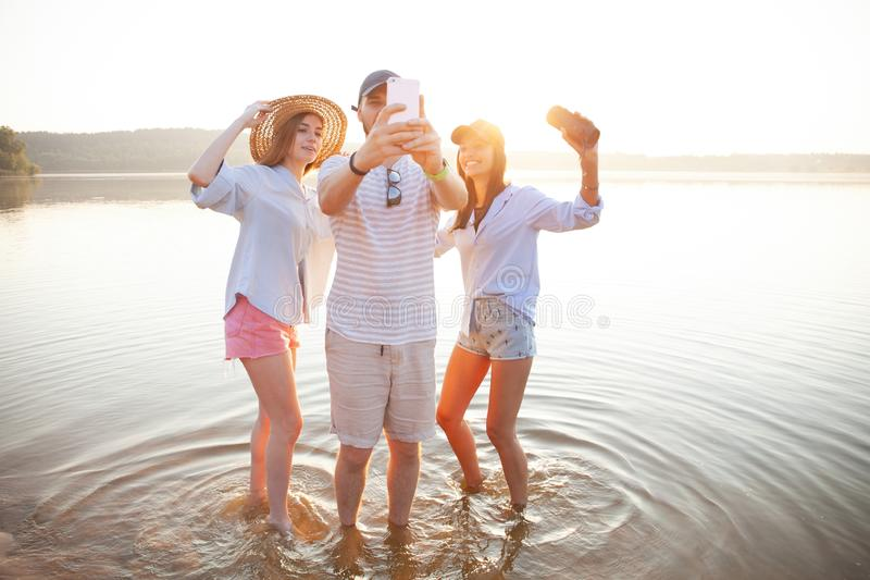 Summer, holidays, vacation and happiness concept - group of friends taking selfie with smartphone. royalty free stock images