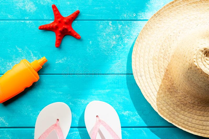 Summer holidays and vacation travel concept. Sunscreen lotion bottle, straw hat, flip flops and red starfish on pastel blue. Background. Top view and copy space royalty free stock photo