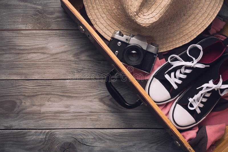 Summer holidays and vacation travel concept. Vintage camera, straw hat and sneakers in old suitcase on wooden background. Top view stock photo