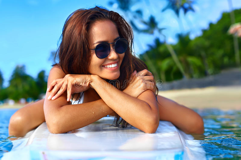 Summer Holidays. Woman On Surfing Board. Travel Vacation. Health. Summer Holidays. Close Up Of Happy Smiling Young Woman In Bikini On Surfing, Surf Board In Sea stock photos