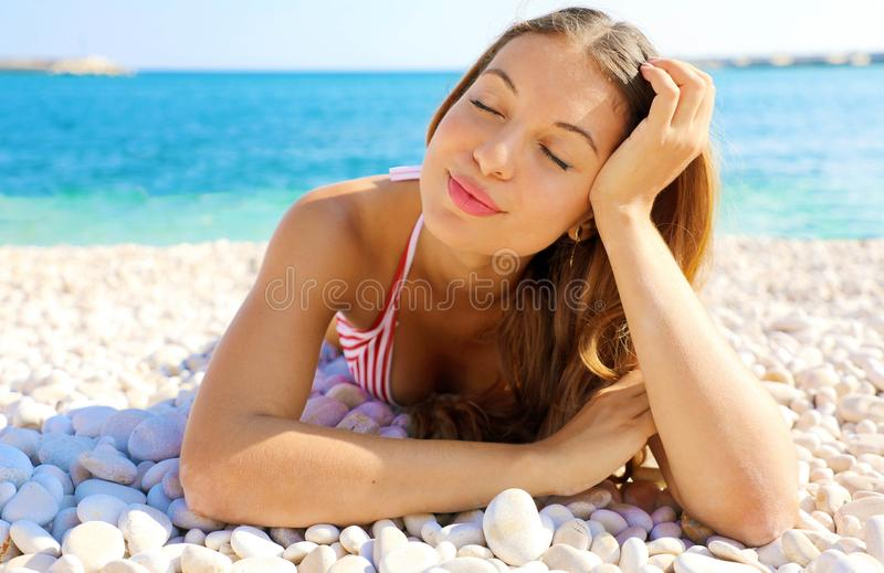 Summer Holidays. Young woman enjoying relax lying on the beach with closed eyes royalty free stock images