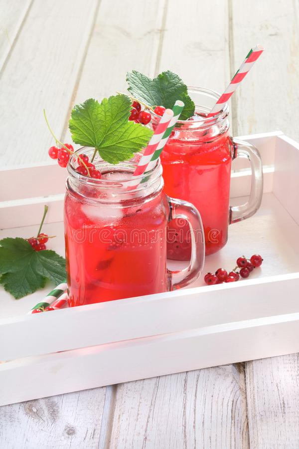 Summer homemade red currant lemonade in a mason jar with decor of berry in tray on rustic table. Close up. Summer homemade red currant lemonade in a mason jar royalty free stock photography
