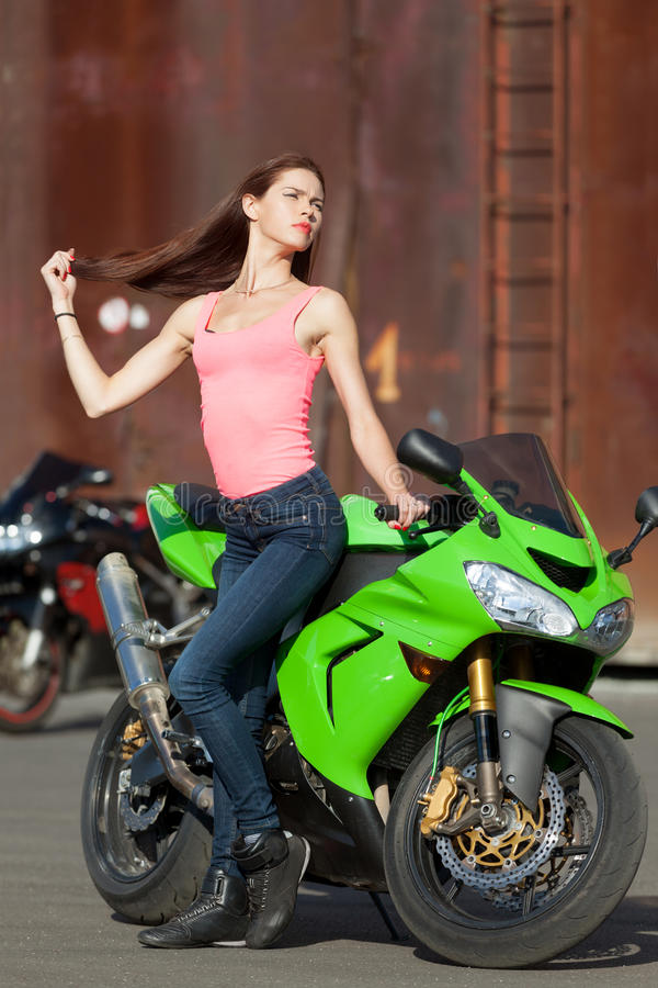 Summer hot. Young attractive girl waiting for her biker to come stock photo