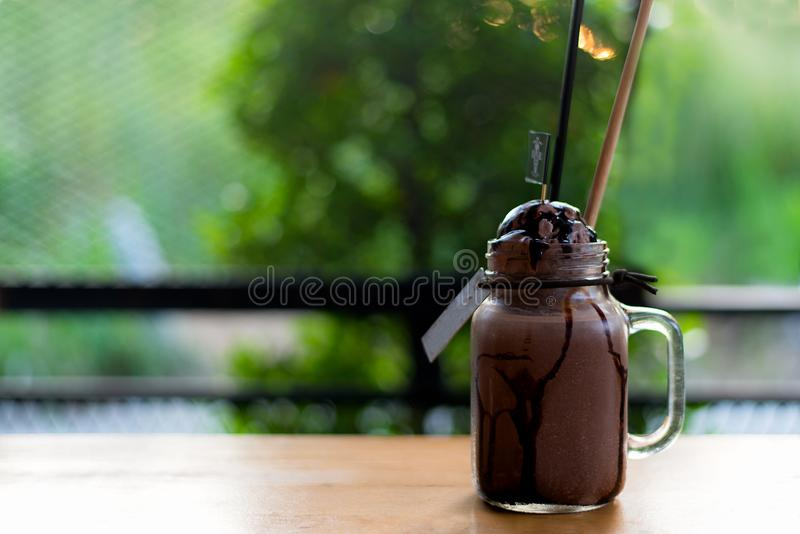 Summer ice fresh drink. Chocolate milkshake with ice cream and whipped cream, marshmallow served in glass mason jar, royalty free stock photography