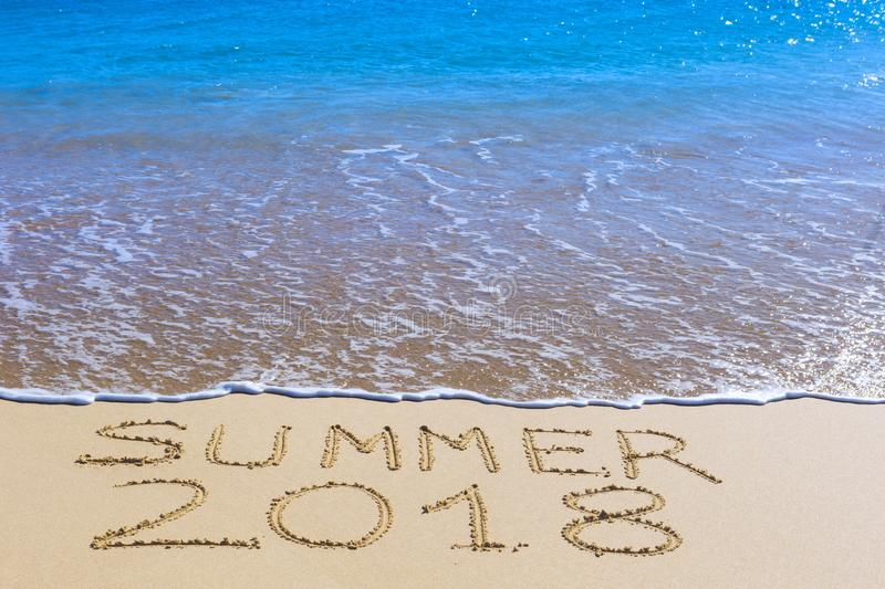 Summer 2018 inscription on wet beach sand. And sea wave on background. Summer season holiday, vacation concept royalty free stock image