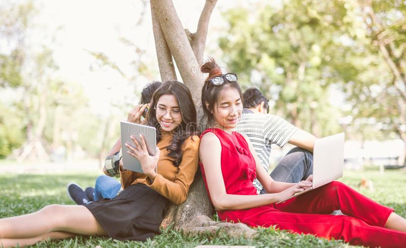 Group of students or teenagers with laptop and tablet computers hanging out. Summer, internet, education, campus and teenage concept - group of students or stock image