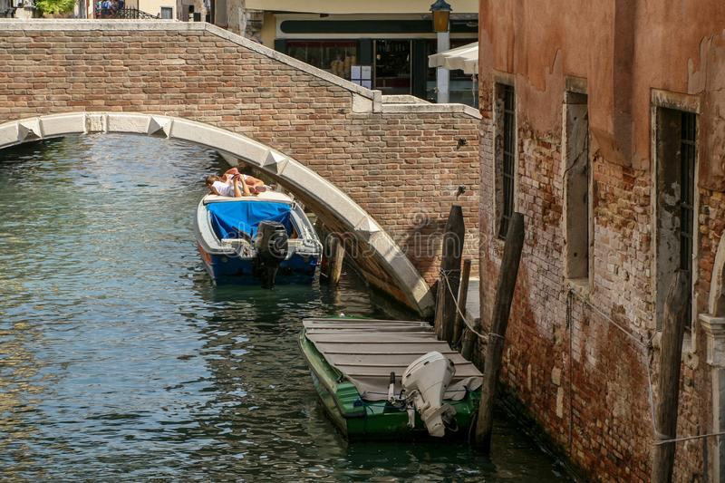 Bridge of red bricks above the channel. Boat on the water. stock images
