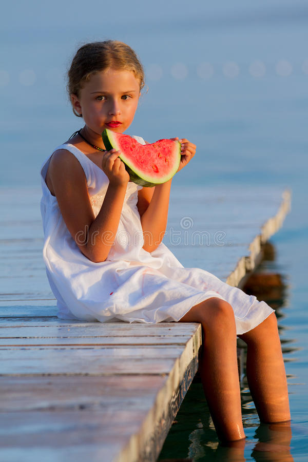 Summer joy, lovely girl eating fresh watermelon on the beach royalty free stock photos