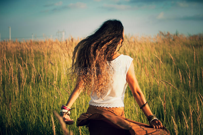 Summer joy. Young woman run in summer field of grass retro colors back shot royalty free stock photo