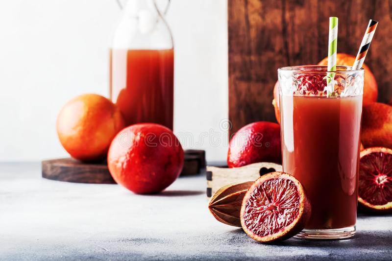 Summer juice or non-alcoholic refreshing healthy cocktail or drink from freshly squeezed red Sicilian orange, bright light table royalty free stock photography