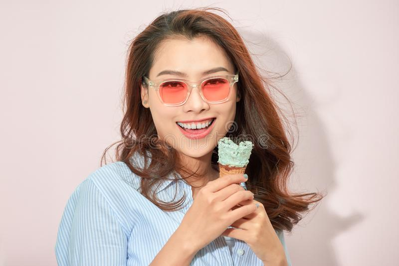 Summer, junk food and people concept - young woman or teenage girl in sunglasses eating ice cream royalty free stock image
