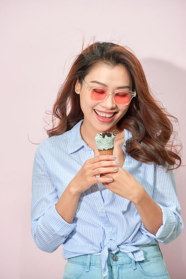 Summer, junk food and people concept - young woman or teenage girl in sunglasses eating ice cream stock images