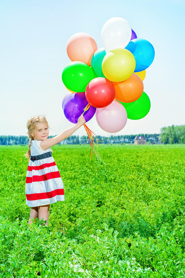 Summer kid. Happy little girl with a bunch of colorful balloons on a summer meadow royalty free stock image