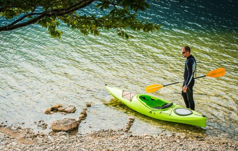 Summer Lake Kayaking Time. Caucasian Men and His Kayak on the Rocky Lake Shore. Water Sport Theme royalty free stock images