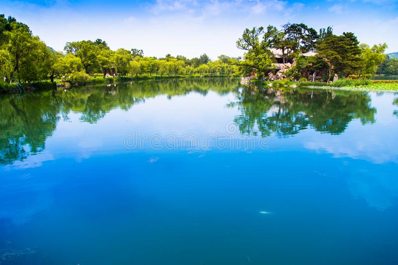 Summer lake light and water color. In summer, white clouds float in the clear sky, blue sky and white clouds are reflected on the calm lake surface, and trees royalty free stock photo