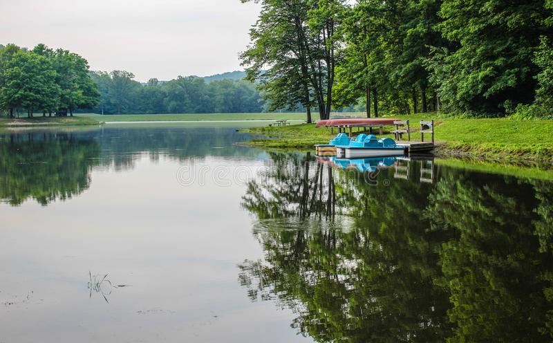 Summer Lake At Ohio State Parks. Paddleboats and canoes line the shore of the lake at Scioto State Park in Chillicothe, Ohio royalty free stock photography