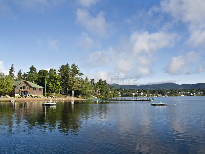 Summer in Lake Placid. Beautiful view of the Mirror Lake, located in Lake Placid (Adirondack Mountains National Park - New York) with reflections of the clouds royalty free stock photography