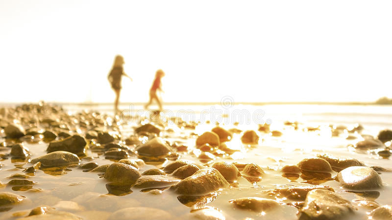 Two kids playing at the beach. Two children playing at the beach of a lake. Pebbles in the foreground. Children blurred in the background. Scenery flooded in stock image
