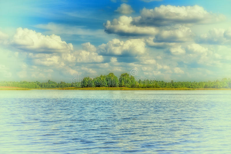Summer landscape with cumulus clouds on the lake. royalty free stock photography