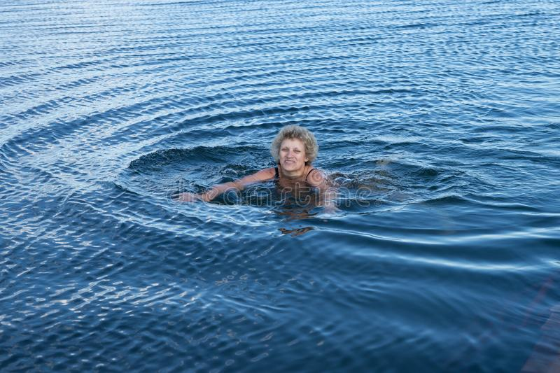An elderly woman is swimming in the blue water. stock image