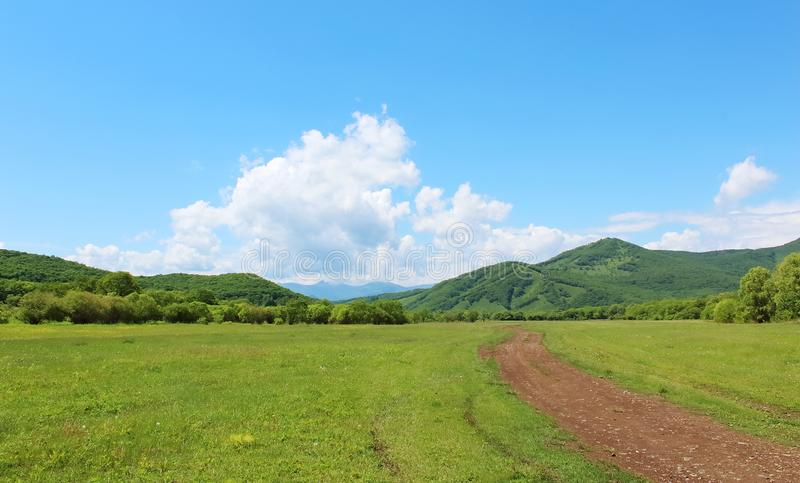 Summer landscape with green grass, hills, road and clouds. Sanny summer landscape with green grass, hills, road and clouds royalty free stock photos