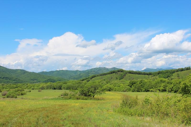 Summer landscape with green grass, hills road and clouds. Sanny summer landscape with green grass, hills, road and clouds royalty free stock photo