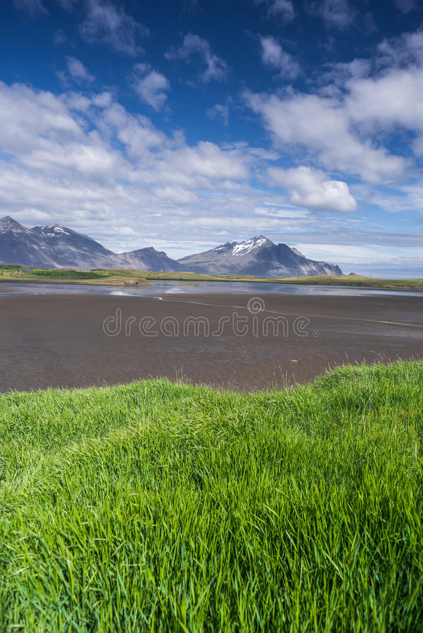 Summer landscape with green grass and mountains in Iceland. Summer landscape with green grass and beautiful sky on a sunny day. Swamp at the bottom of the Bay royalty free stock images