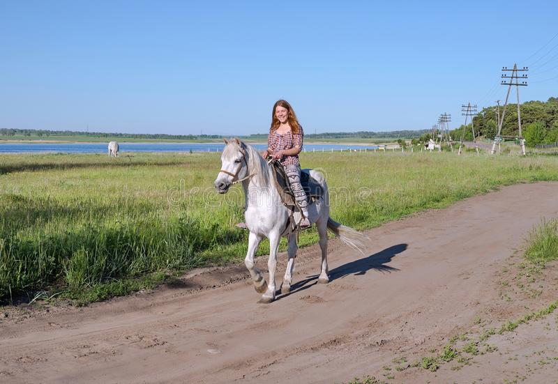 Happy girl riding on horseback, on a rural road, against the backdrop of a lake. royalty free stock photography